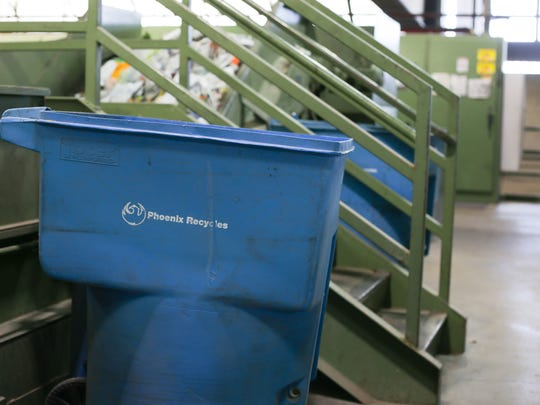 Recyclable goods get placed in bright blue bins lining