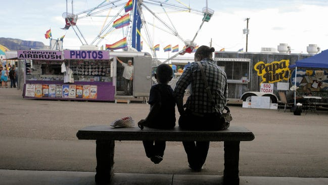 In this 2014 file photo, a boy and woman sit on a bench with a bag of popcorn near the midway at the Otero County Fairgrounds. The 2016 Fair is Aug. 24 through Aug. 27.