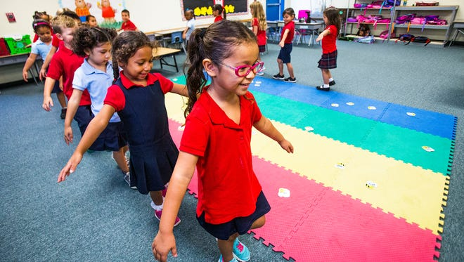 Alyssa Fausto leads Tisha Alvarez's kindergarten class in a game of Busy Bees at Crown Charter School in Litchfield Park.