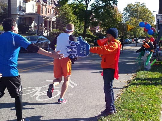Jermaine Davis, 13, holds out a foam hand for marathoners to hit as they run past him Sunday morning, Oct. 18, 2015, on Buttles Avenue at Goodale Park in Columbus. Davis was a patient champion at the Nationwide Children's Hospital Columbus Marathon.