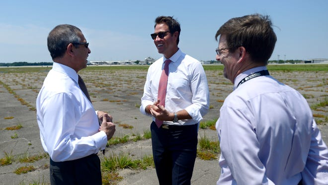 Ashok Kumar Mirpuri, Singapore ambassador to the United States, left, chats with Mayor Ashton Hayward and Daniel Flynn, assistant airport director-operations, on Monday at Pensacola International Airport while looking over the future site of the VT Mobile Aerospace Engineering, Inc. maintenance facility. Construction for the 160,000 square foot facility is scheduled to begin January 2016 and be operational early 2017. It will employ 300 workers with the possibility to expand to 500 according to Bill Hafner, VT MAE President.