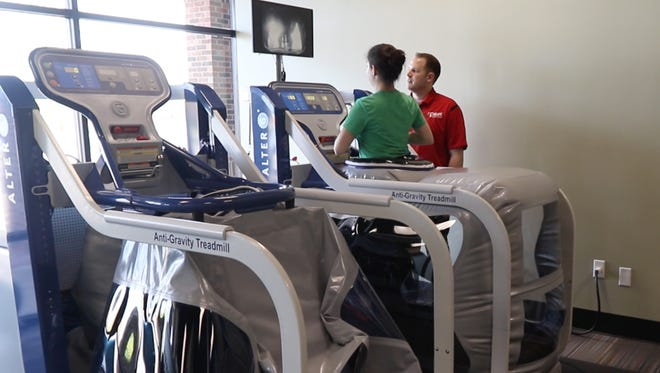 Sarah Taddeo, reporter at the Democrat and Chronicle, tries out the anti-gravity treadmill at Agape Physical Therapy in Webster. Telling her about the ways it can be used for patients is Adam Krahmer, physical therapist.