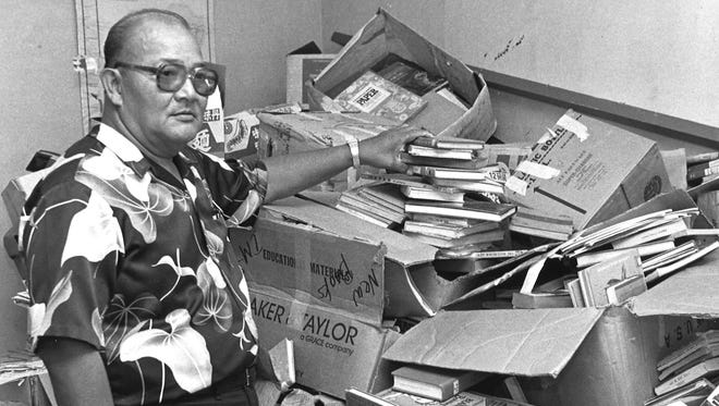 In this April 1988 file photo, Inarajan Commissioner Jaime Paulino stands beside a large stack of books in a room he planned to convert to a mini library.