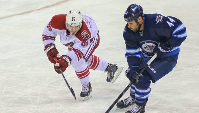 Winnipeg Jets defenseman Zach Bogosian (44) battles for the puck with Phoenix Coyotes forward Mikkel Boedker (89) during the third period at MTS Centre. The Jets won 3-2 in overtime.
