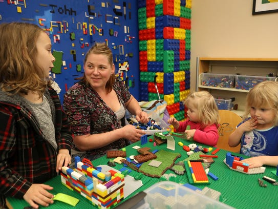 Amanda Hatherley, center, plays with Legos alongside her stepdaughter Skyler Malone-Long, from left, daughter, Izzabella Long, and stepdaughter, Callie Malone-Long, at the Redding Library