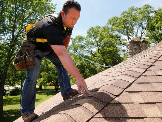 James Shaw performs an inspection of the new roof atop
