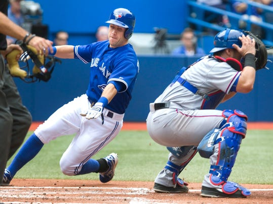 Toronto Blue Jays Steve Tolleson goes around Texas Rangers' catcher Geovany Soto to score on a hit by Blue Jays Jose Reyes during second inning of baseball game in Toronto on Sunday, July 20, 2014. (AP Photo/The Canadian Press, Fred Thornhill)