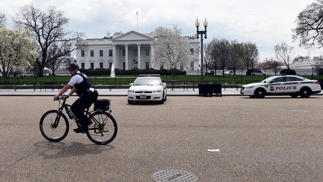 A Secret Service rides his bike on Pennsylvania Avenue outside the White House in Washington, D.C.
