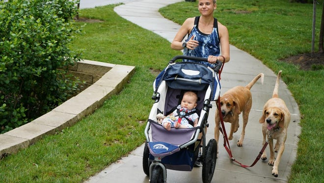 Andrea Berardi runs with her dogs and a stroller carrying her daughter, Simone. She said the findings of the study make her more determined to keep exercising and breastfeeding.