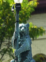 Bear sits on top the light pole of the water fountain