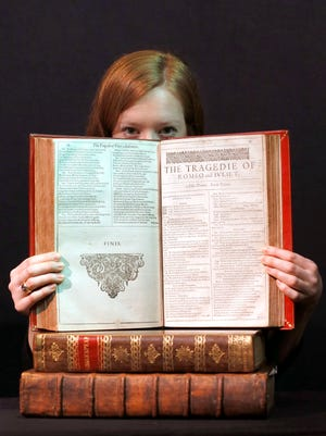 """A Christie's member of staff displays an unrecorded copy of the First Folio, the first collected edition of Shakespeare's plays, widely considered the most important literary publication in the English language, in London, Wednesday, March 16, 2016. The book contains 36 plays, 18 of which appear here for the first time in print, and is estimated at 800,000-1.2 million UK pounds (1,127,760- 1.69 million US dollars). William Shakespeare died 400 years ago, but his stock has never been higher. To coincide with the anniversary of the Bard's death, Christie's is selling copies of the first four editions of his plays - a collection the auctioneer's head of books, Margaret Ford, calls """"the holy grail of publishing."""""""