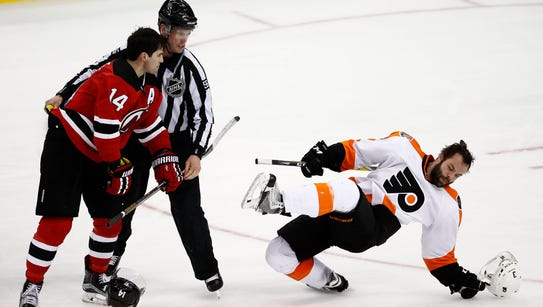 Flyers defenseman Radko Gudas, right, falls down after