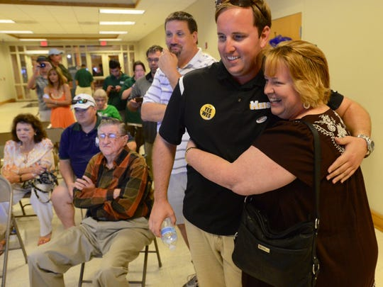 Wesley Meiss gets a hug from his mother, Roxanne, after winning the mayoral race against longtime mayor Guy Thompson.