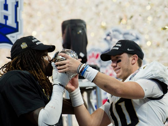 UCF quarterback McKenzie Milton (10) holds out the Peach Bowl trophy as UCF linebacker Shaquem Griffin (18) kisses it after UCF defeated Auburn 34-27 in the Peach Bowl on Monday, Jan. 1, 2018, at Mercedes-Benz Stadium in Atlanta, Ga.