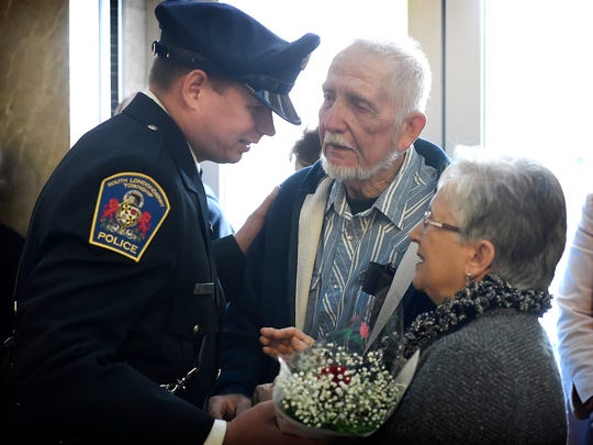 Joanna and Frank Pierce are presented with flowers by Rob Lighty of the S. Londonderry Police Department during an annual ceremony to honor law enforcement that have died in the line of duty. The Pierce's daughter, Sgt. Sheryl Pierce died Sept. 14, 2013. Sergeant Sheryl Pierce died as the result of Hepatitis C, which she contracted in 1994 while subduing a man who was bleeding profusely.