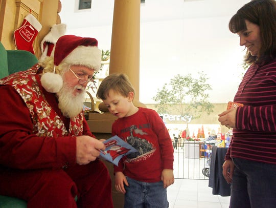 Santa shows a book to Nathan Hooper, 4, of Tiffin,
