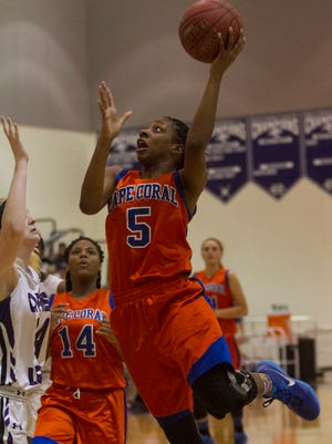 Cape Coral's Jazzmyn Simmons takes a shot over Cypress Lake's Emily Slone in the 5A-3 girls basketball regional semifinal at Cypress Lake High School on Tuesday, February 10, 2015.