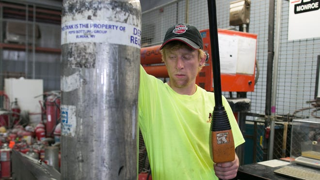 Eric Walzer uses a hydrostatic testing station to re-qualify a fire extinguisher at Monroe Extinguisher.