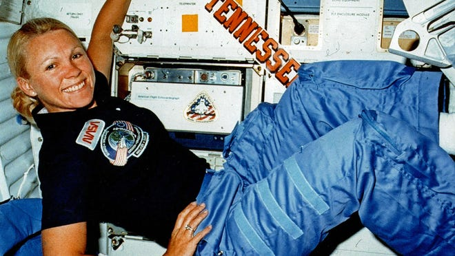 Rhea Seddon floats next to an echocardiography machine used in space experiments (and a Tennessee bumper sticker) during her first flight.