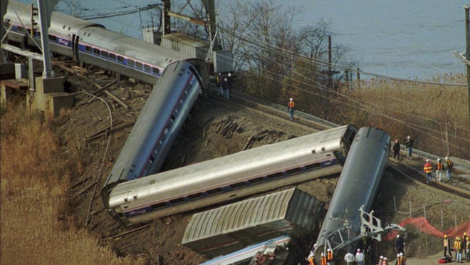 In this Nov. 23, 1996 file photo, emergency workers stand near an Amtrak train which derailed and fell down an embankment into a marshy area after sideswiping a southbound Amtrak train in a remote area of Secaucus. While the issue of building a new rail tunnel under the Hudson River and refurbishing the existing 105-year-old tunnel has gained traction in recent weeks after a series of delays, it is far from the only chokepoint on the 457-mile Northeast corridor between Washington, D.C. and Boston. These include regular delays at the Portal Bridge caused by the 105-year-old swing bridge not closing properly after opening for boats.