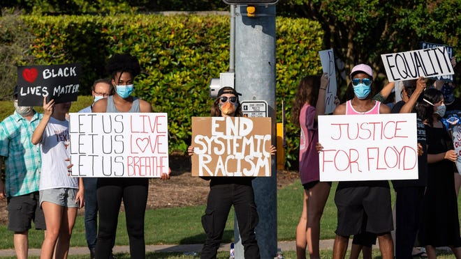 From left in the front, Marilyn Nzoiwu, Korina Lurie and William Nzoiwu hold signs supporting the Black Lives Matter movement on Tuesday.  There has been a peaceful protest at the intersection of Red Bud Lane and Forest Creek Drive in Round Rock nightly since Sunday.