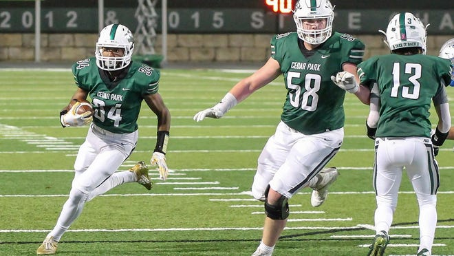 Cedar Park tackle Luke Williams, right, clears the way for receiver Josh Cameron on an end-around in a playoff win over McCallum last season. Williams returns as one of the top tackles in the Austin area.