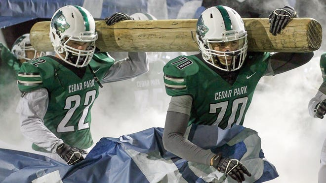 Luke Benavides, right, and Will Lovell carry the timber as Cedar Park's football team takes the field before a Class 5A Division I first-round playoff game against McCallum. The football team won one of the Timberwolves' seven district titles in the 2019-20 school year.