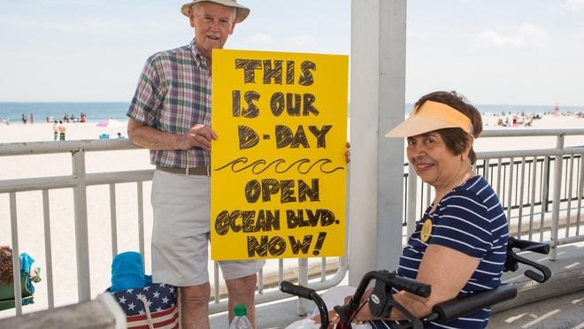 Pete and Anita Hinkle of Merrimack hold a sign in support of reopening the state's beach and Ocean Boulevard in Hampton on Saturday, June 6. Pete was previously a state representative from Merrimack.