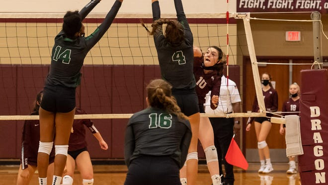 Round Rock's Mackenna Gardner takes a shot for the Dragons, challenged by Nia Cummings, left and Megan Woods of Cedar Park. Round Rock won the nondistrict volleyball match at home in four sets Tuesday.