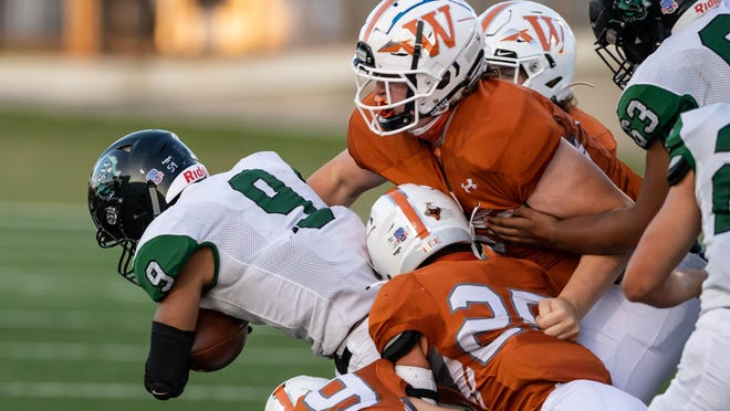 San Antonio Southwest's Lloyd Young is stuffed by, from left, Westwood's Jack Ziebell, Brian Lee and Ryan Lass during the Warriors' season-opening 37-8 win at Kelly Reeves Stadium Thursday. The Warrior defense forced six tournovers in the victory.