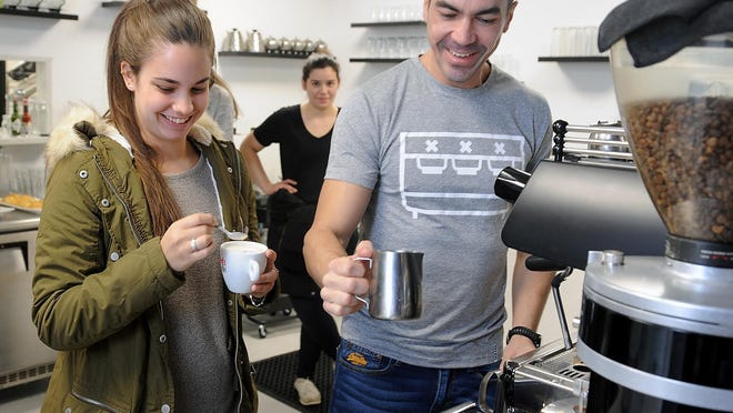 Sofa Cafe owner Diego Gonzales teaches employees how to steam milk.