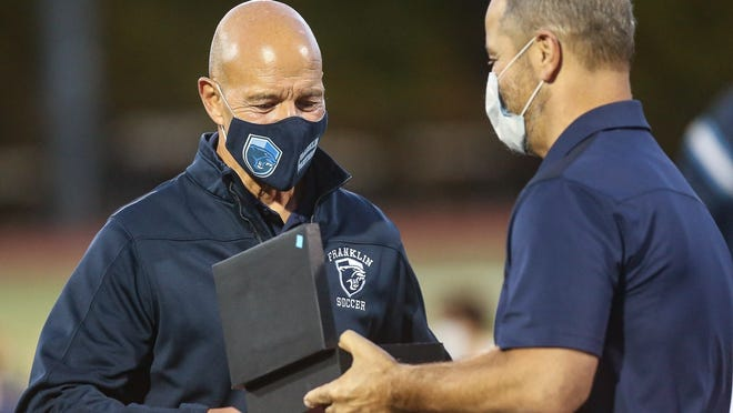 Franklin athletic director Tom Angelo (right) gives a service award to Franklin boys soccer head coach Fran Bositis during a ceremony after the boys soccer game against King Philip at Franklin High School on Wednesday. This is Bositis' 50th year of coaching soccer at Franklin High School.