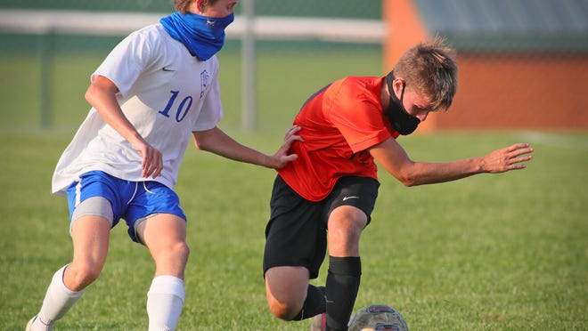 Tecumseh's Dylan Brewer controls the ball while Adrian's Aiden Smith guards during Tuesday's match.