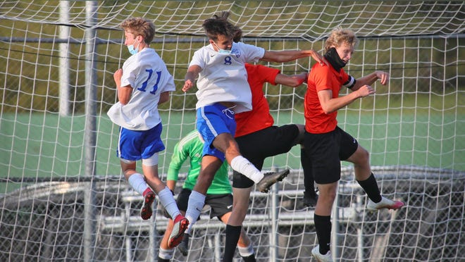 Adrian's Freddy Cruze (11) and Evan Johnson (8) and Tecumseh's Kyle Kemppainen (back) and Ryan Frazzini (right) go up for the ball during a corner kick in Tuesday's game.