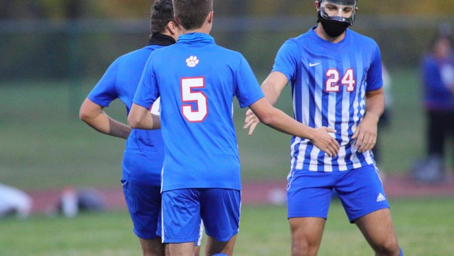 Lenawee Christian's Gabe Henley (24) celebrates a goal with Brennan Griffith (5) during Monday's game against Jonesville.