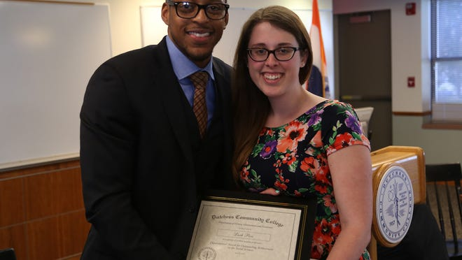 Dutchess Community College sAssistant Professor of History Weldon McWilliams, Ph.D., presents a departmental award for outstanding achievement in the social sciences to student Leah Pica.