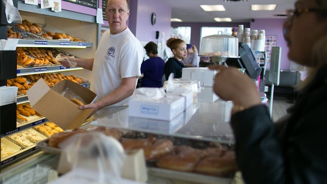 Co-owner Rich Marcello serves a customer at Ridge Donut Cafe in Irondequoit on Monday, April 20, 2015.