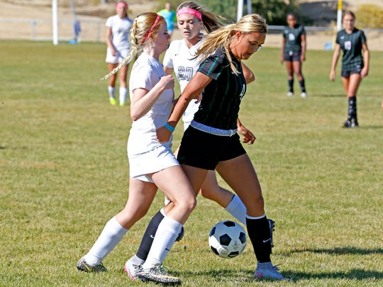 Farmington's Arin Coleman, right, tries to steal the ball during an Oct. 7, 2015, game against Piedra Vista at the Piedra Vista High School soccer fields in Farmington.
