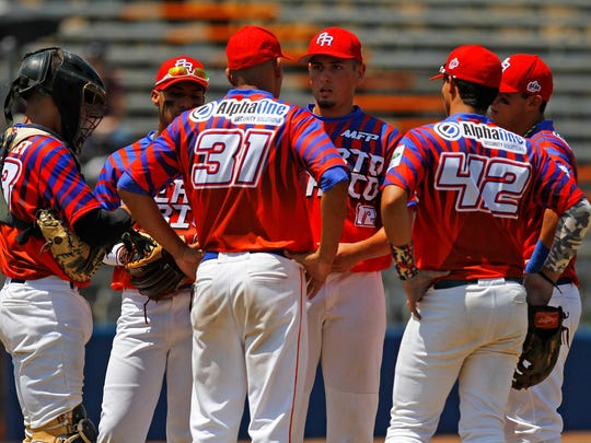 Players on the MFP Arecibo team meet on the mound to talk to pitcher Ryan Munoz on Saturday in Game 4 of the Connie Mack World Series against EnFuego Elite at Ricketts Park in Farmington.