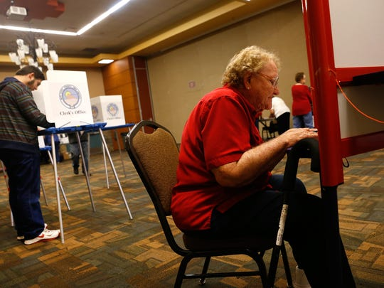 Michael Rowe, left, and Belva Christensen fill out their ballots on Tuesday at the Farmington Civic Center.