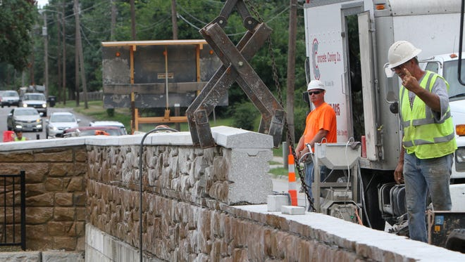 Above: Workers on Tuesday remove a section of the wall that obstructed drivers' view of oncoming traffic at Jefferson Avenue nd Bennett Street.