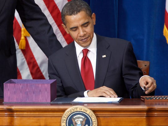 This Feb. 17, 2009 file photo shows President Barack Obama picking up the first pen to sign his economic stimulus bill, a costly spending bill that expanded the deficit but helped stabilize the economy.