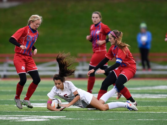 Frida Fortier of Benilde-St. Margaret's stumbles while surrounded by Apollo players during the first half of the Thursday, Oct. 27, game at Husky Stadium in St. Cloud.