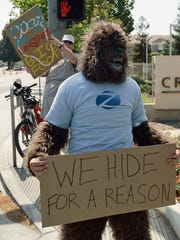 A man in an ape costume is seen outside a hotel where a media conference is held announcing the claim that a deceased Bigfoot was found in Georgia.