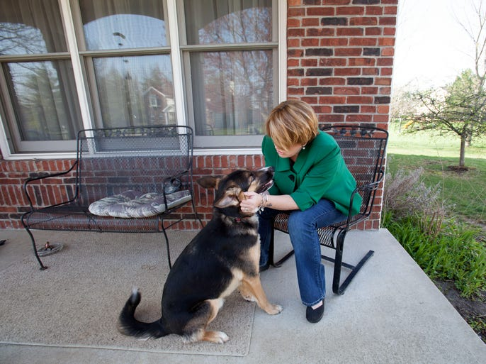 """Justin Phillips lost her son, Aaron Sims, last October due to a heroin overdose.  She plays with his dog Cain on the front porch of her home.  """"He is a part of Aaron"""", she says."""