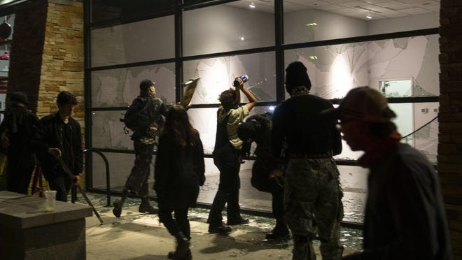 Protesters break windows in store fronts along Seventh Avenue in Eugene on May 29 in what started as a protest over the killing of George Floyd in  Minneapolis, Minnesota. [Chris Pietsch/The Register-Guard file] - registerguard.com
