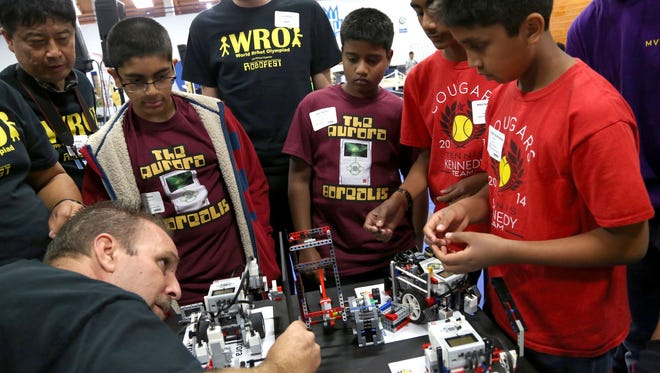 Judge Mike Dobbyn, 47, of Hamtramck, Mich., inspects various robots before competition at the World Robot Olympiad  at  Lawrence Technological University in Southfield, Mich., on Saturday.