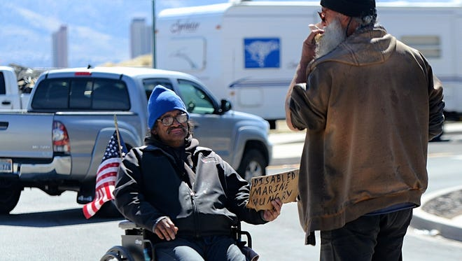 Boyd Renken, 67, right, Jesse Hernandez, 60, remain on a traffic island as Hernandez solicits donations from drivers passing by at a shopping center on North McCarran Boulevard and Northtowne Lane in north Reno on March 29, 2018.
