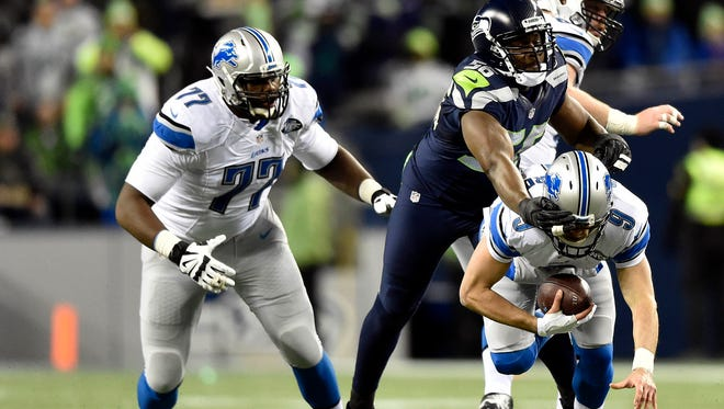 Seahawks defensive end Cliff Avril brings down Detroit quarterback Matthew Stafford during the first half.