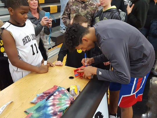 Spring Grove's Eli Brooks signs autographs for Red Lion fans after Tuesday's game.